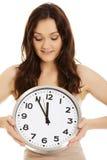 Uśmiechnięta kobieta trzyma dużego zegar Obrazy Royalty Free