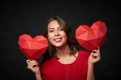 Uśmiechnięta kobieta trzyma dwa poligonalnego kierowego kształt Obrazy Stock