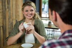 Uśmiechnięta kobieta trzyma filiżankę podczas gdy patrzejący mężczyzna w kawiarni Obrazy Stock