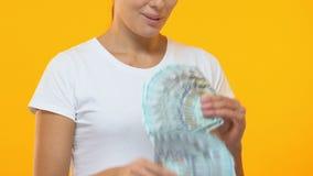 Uśmiechnięta kobieta trzyma wiązki dolary, pomyślny uruchomienie projekt, pieniądze zbiory