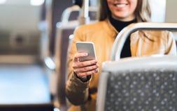 Uśmiechnięta kobieta używa smartphone w pociągu, metrze, autobusie lub tramwaju, zdjęcia stock