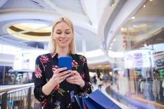Uśmiechnięta kobieta używa telefon komórkowego w centrum handlowym obrazy royalty free
