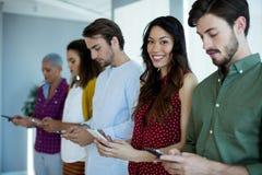 Uśmiechnięta kobieta używa telefon komórkowego z ich kolegami w biurze fotografia royalty free