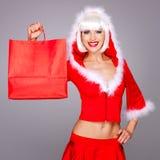 Uśmiechnięta kobieta w śnieżnym dziewiczym kostiumu trzyma torba na zakupy obrazy stock