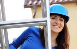 Uśmiechnięta kobieta w błękitnym hełmie na aluminiowej drabinie Fotografia Stock