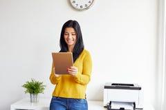 Uśmiechnięta kobieta w biurowym działaniu na cyfrowej pastylce fotografia royalty free