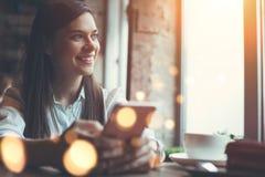 Uśmiechnięta kobieta w cukiernianym używa telefonie komórkowym i texting w ogólnospołecznych sieciach, siedzi samotnie obrazy stock