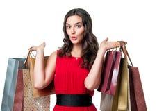 Uśmiechnięta kobieta w czerwieni sukni z torba na zakupy Zdjęcie Royalty Free