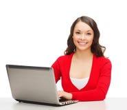 Uśmiechnięta kobieta w czerwieni ubraniach z laptopem zdjęcia royalty free