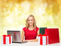Uśmiechnięta kobieta w czerwonej koszula z prezentami i laptopem fotografia stock