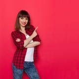 Uśmiechnięta kobieta W Czerwonej Lumberjack koszula Wskazuje Obrazy Royalty Free