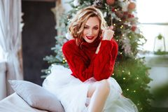 Uśmiechnięta kobieta w czerwonym pulowerze nad choinki tłem zdjęcia royalty free