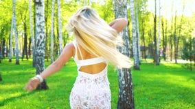 Uśmiechnięta kobieta w eleganckim kostiumu i akcesoriach tanczy bosego w brzoza gaju zbiory