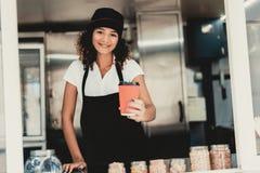 Uśmiechnięta kobieta w fartuch pozycji w jedzenie ciężarówce fotografia stock