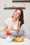 Uśmiechnięta kobieta w piżamach je organicznie śniadanie zdjęcia royalty free