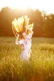 Uśmiechnięta kobieta w polu przy zmierzchem z latającym włosy obrazy stock