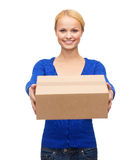 Uśmiechnięta kobieta w przypadkowych ubraniach z pakuneczka pudełkiem Zdjęcia Royalty Free