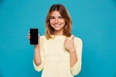 Uśmiechnięta kobieta w pulowerze pokazuje pustego smartphone ekran obrazy stock