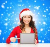Uśmiechnięta kobieta w Santa kapeluszu z prezenta i pastylki komputerem osobistym Fotografia Stock