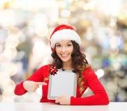 Uśmiechnięta kobieta w Santa kapeluszu z prezenta i pastylki komputerem osobistym Fotografia Royalty Free