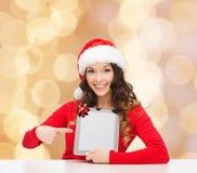 Uśmiechnięta kobieta w Santa kapeluszu z prezenta i pastylki komputerem osobistym Zdjęcie Stock