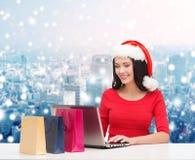 Uśmiechnięta kobieta w Santa kapeluszu z torbami i laptopem Zdjęcia Stock