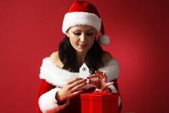Uśmiechnięta kobieta w Santa pomagiera kapeluszu Claus i Santa odziewa pomagać z etykietką na prezenta pudełku Zdjęcia Stock