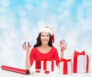 Uśmiechnięta kobieta w Santa pomagiera kocowania kapeluszowych prezentach Fotografia Royalty Free