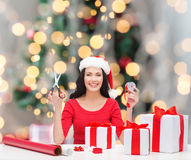 Uśmiechnięta kobieta w Santa pomagiera kocowania kapeluszowych prezentach Fotografia Stock