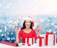 Uśmiechnięta kobieta w Santa pomagiera kocowania kapeluszowych prezentach Zdjęcia Stock