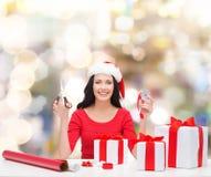 Uśmiechnięta kobieta w Santa pomagiera kocowania kapeluszowych prezentach Obrazy Royalty Free