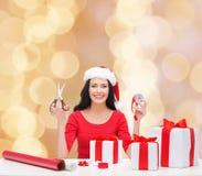 Uśmiechnięta kobieta w Santa pomagiera kocowania kapeluszowych prezentach Zdjęcie Royalty Free