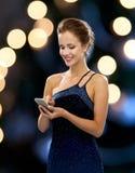 Uśmiechnięta kobieta w wieczór sukni z smartphone Fotografia Stock