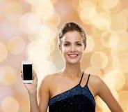 Uśmiechnięta kobieta w wieczór sukni z smartphone Fotografia Royalty Free
