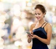 Uśmiechnięta kobieta w wieczór sukni z smartphone Obrazy Royalty Free