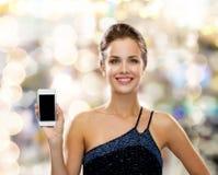 Uśmiechnięta kobieta w wieczór sukni z smartphone Zdjęcia Royalty Free