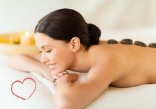 Uśmiechnięta kobieta w zdroju salonie z gorącymi kamieniami Zdjęcie Royalty Free