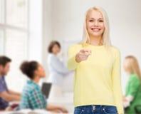 Uśmiechnięta kobieta wskazuje palec przy tobą zdjęcie stock