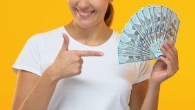 Uśmiechnięta kobieta wskazuje palec przy wiązką dolary, tłum zakłada usługi zbiory wideo