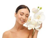 Uśmiechnięta kobieta z białym storczykowym kwiatem Obrazy Stock