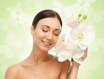 Uśmiechnięta kobieta z białym storczykowym kwiatem Zdjęcia Stock