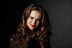 Uśmiechnięta kobieta z długim falistym brown włosy na ciemnym tle zdjęcia stock