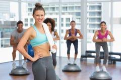 Uśmiechnięta kobieta z dysponowanymi ludźmi wykonuje kroków aerobiki ćwiczy Fotografia Royalty Free