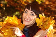Uśmiechnięta kobieta z jesień liśćmi w rękach Fotografia Royalty Free