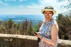 Uśmiechnięta kobieta z kapeluszem, szkłami i telefonem w rękach plenerowych, Fotografia Stock