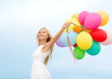 Uśmiechnięta kobieta z kolorowymi balonami outside Fotografia Stock