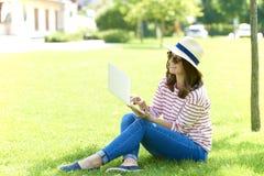 Uśmiechnięta kobieta z laptopem plenerowym fotografia stock