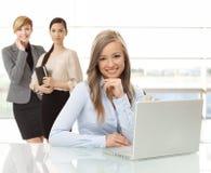 Uśmiechnięta kobieta z laptopem przy biurem fotografia stock