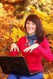 Uśmiechnięta kobieta z laptopem w jesień parku Zdjęcie Royalty Free