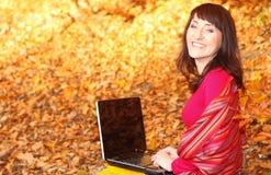 Uśmiechnięta kobieta z laptopem w jesień parku Fotografia Royalty Free